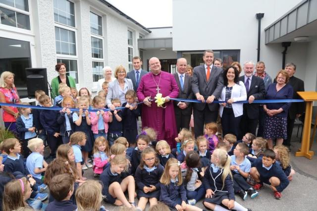 Junior Infants, guests and local politicians help the Bishop with the official opening.  From left (and third to the right of the Bishop) are: Mrs Dorothy Verplancke, Mrs Harriet Pritchard (Principal), Councillor James O'Donovan, the Bishop, Jim Daly, T,.D., Michael McCarthy, T.D. Councillor Margaret Murphy-O'Mahony, and Andrew Coleman (Chairperson of the Board of Management). Photo:  Trevor Collins