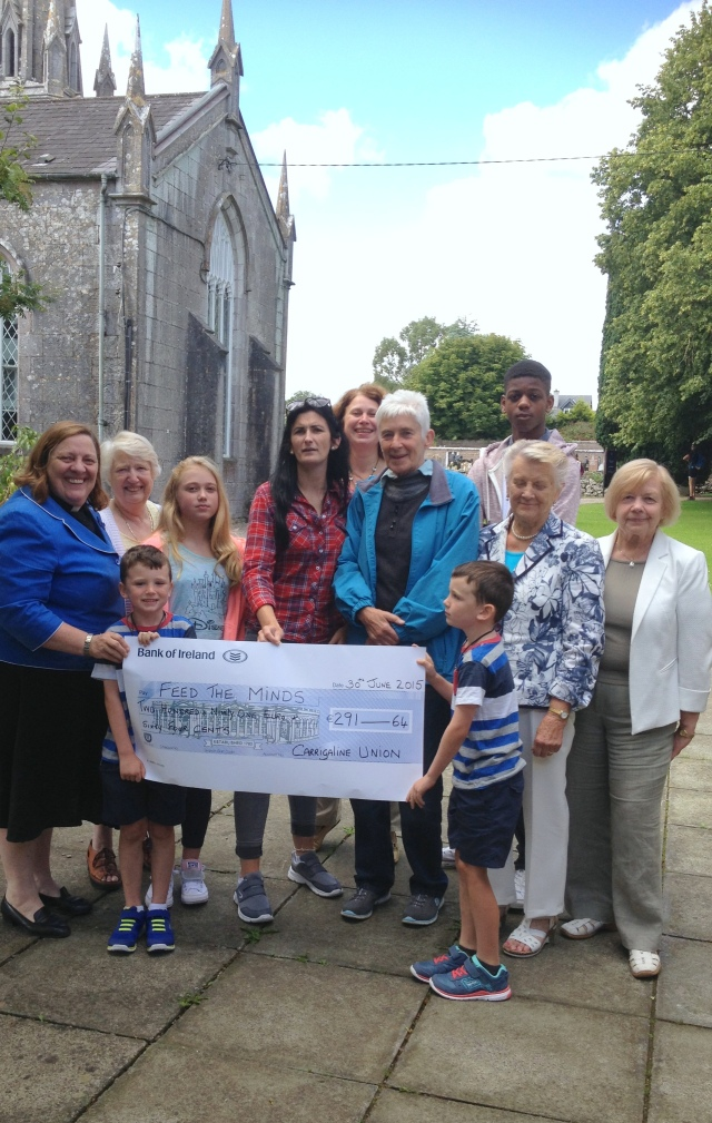 Some parishioners from Carrigaline Union of Parishes in the Diocese of Cork holding a cheque for €291.64 made out to the charity 'Feed the Minds' (FTM), with (on the left) their rector, the Reverend Elaine Murray.