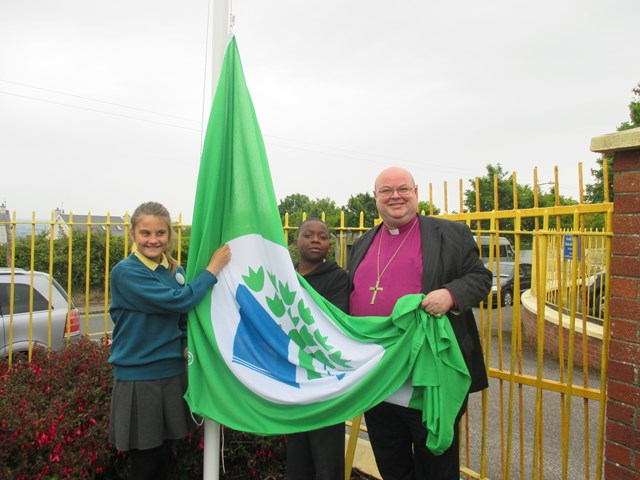 Assisted by children from South Abbey National School, Youghal County Cork, Bishop Paul Colton prepares to raise the school's first Green Flag.