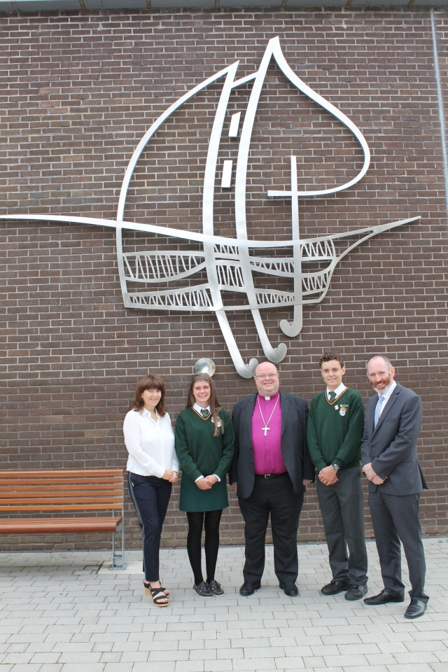 Underneath the modern representation of the Ashton School crest on the wall of the sports hall are (l-r) Ms Anne-Marie Hewison (Deputy Principal), Ally Lynch, Head Girl, the Bishop, Steven Jermyn, Head Boy and Adrian Landed, Principal. The crest features the Bishop's Mitre and the Mulberry leaf, and also the ship in the harbour of Cork from the City of Cork coat of arms, as well as a hockey stick formed, with the sail, into the Cross.