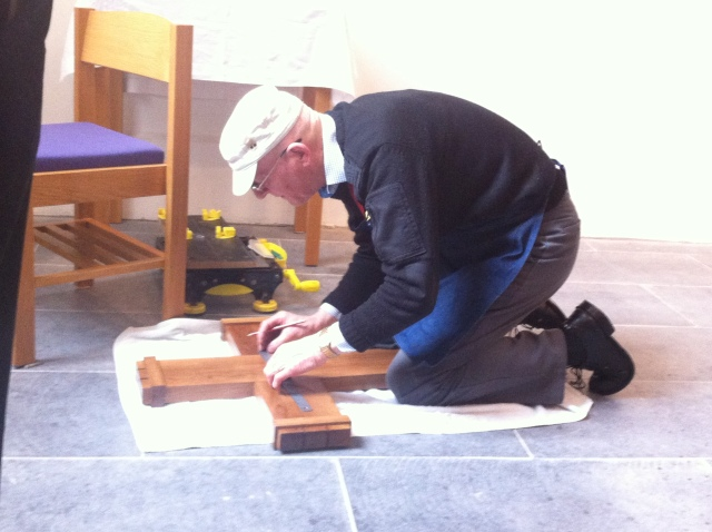 Pat Culleton prepares the cross for mounting on the chapel wall