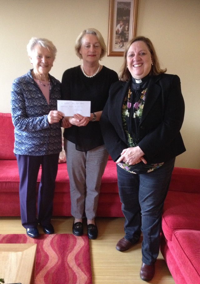 Joyce Loney (left) presents a cheque to the administrator of Cuanlee, with her rector, the Reverend Elaine Murray (right).